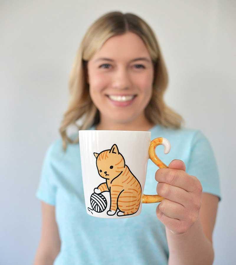 Taza de gato, mujer sosteniendo